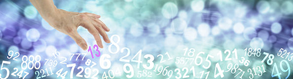 Number 13 Unlucky for some. Wide blue bokeh banner with white numbers randomly placed along the bottom and a female hand choosing the number 13 royalty free stock photos