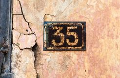 Number 35 on wall sign, rusty and weathered. Number 35 on wall sign, rusty and weathered royalty free stock photo