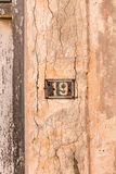 Number 19 on wall sign, rusty and weathered. Number 19 on wall sign, rusty and weathered stock images