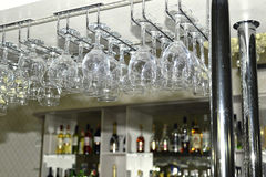 A number of washed glasses hung to dry in the bar Royalty Free Stock Image