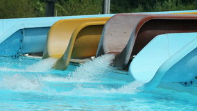 Number of water slides with kids rushing down. Group of people going to vacation at pool where they are a lot of waterslides and pools, attractions and amusement stock video