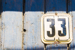 Number 33 on the wooden blue crack wall Royalty Free Stock Photo