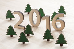 Number 2016. And wooden trees on brown wooden background (new year 2015-2016 Stock Photography