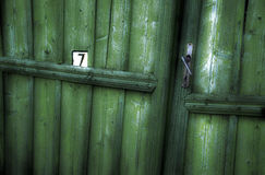Number 7 written on an old weathered green door. Vintage Royalty Free Stock Photo