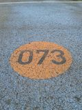 Number 073 written on tarmac road Royalty Free Stock Images