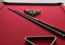 Numbered Billiard balls on a red pool table with two cues and a black ball rack. Numbered billiard balls on a red felt pool table with two pool cues and a black stock photo