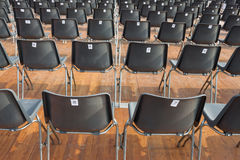 Numbered chairs. Empty numbered chairs lined up Stock Photo