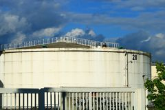 Numbered industrial water tank behind a metal barrier royalty free stock image