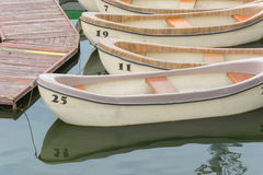 Numbered pleasure rowing boats tied up on a lake Stock Photos