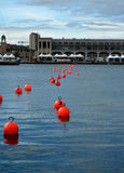 Numbered Red Buoys. The bright numbered red buoys are a navigational assistant when docking. In this case, they are also direct the view of the passerby to the Stock Image