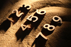Numbering On Sand. Wooden digits as calculator on sand background with shadow Royalty Free Stock Photo