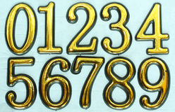 Numbers 0 to 9. Golden bright numbers on a light blue background. Numbers 0 to 9 Royalty Free Stock Images