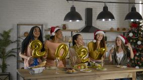 Numbers foil, 2021 girls having fun in the kitchen on Christmas Eve. party with friends 4K. Numbers from foil, 2021 girls having fun in the kitchen on Christmas stock video footage