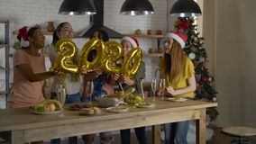 Numbers from foil, 2020 girls having fun in the kitchen on Christmas Eve. party with friends 4K stock video footage