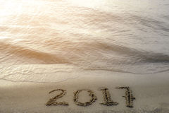 Numbers 2017 handwritten in golden sand on the beach next to the Stock Photo