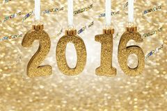 2016 numbers hanging from ribbon with twinkling gold background Royalty Free Stock Photography