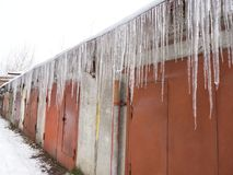 Numbers of ice icicles hang under the roofs of the garages. Danger of falling and injury stock images