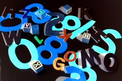 Numbers and Letters on Black. Close up of felt cut out numbers and letters with blocks on black background Stock Photography