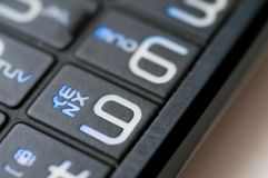 Numbers and letters on an old used mobile phone. On blue color close up Royalty Free Stock Photo
