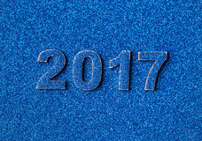Numbers of the new year 2017 laid out on background of blue sparkling shining sequins. Royalty Free Stock Photo