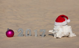 The numbers of the new year 2017 are in the sand and near the sand is pink ball and a large white shell, which is wearing a red Sa Royalty Free Stock Photo