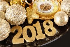2018 numbers with New Years themed gold decor. Shiny 2018 numbers with New Years themed gold decor, baubles and clock, close up on a black charger Stock Image