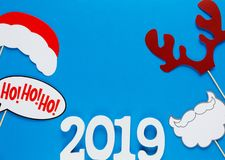 Numbers 2019 and photo booth colorful props for christmas party on blue background. Christmas and New year stock photos