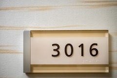 Numbers on plaque, with braille. Number digits 3016 on plaque, with braille translation at the bottom. The plaque is fixed on a wall Stock Photography