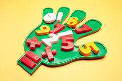 Numbers on Plastic Hand. On Yellow Background stock photography