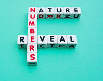 Numbers reveal nature. Text ' nature, numbers, reveal ' inscribed on small white cubes and arranged crossword style with common letters ' n and e ' and isolated Royalty Free Stock Photos