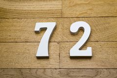 The numbers seventy-two on the wooden parquet floor. The numbers seventy-two on the wooden parquet floor in the background Stock Photo