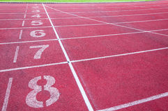 Numbers starting point on red running track,running track and green grass Royalty Free Stock Image