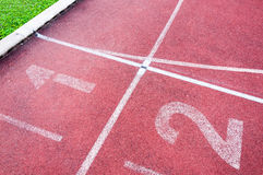 Numbers starting point on red running track,running track and green grass Royalty Free Stock Photos