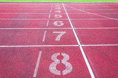 Numbers starting point on red running track,running track and green grass Stock Images