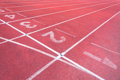 Numbers starting point on red running track,running track and green grass Stock Photo
