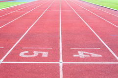 Numbers starting point on red running track,running track and green grass Royalty Free Stock Images