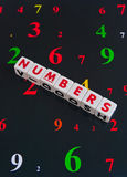 Numbers. Text ' Numbers ' in red uppercase letters on small white cubes presented on a dark background also numbered in various colors Stock Photo