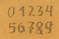 Numbers from 0 to 9 hand-drawn in the beach sand. Abstract. Numbers from 0 to 9 hand-drawn in the beach sand Stock Photos