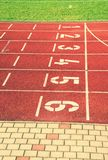 Numbers of tracks. Red running racetrack on the outdoor athletic stadium Royalty Free Stock Photography