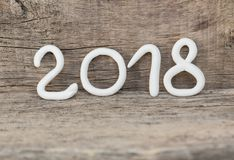 Numbers from white clay forming the number 2018, Element for a postcard new year 2018 on a rustic wooden background. stock image