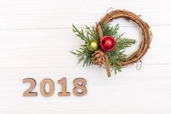 The numbers 2018 and wreath of pine branch and cone on white wooden background royalty free stock photography