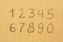 Numbers written on a sandy beach. Education. Stock Images