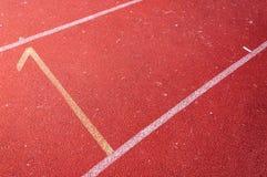 Numera el punto inicial en la pista corriente roja, pista corriente Fotografía de archivo libre de regalías