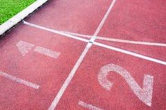 Numera el punto inicial en pista corriente roja, pista corriente e hierba verde Fotos de archivo libres de regalías
