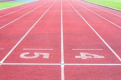 Numera el punto inicial en pista corriente roja, pista corriente e hierba verde Imágenes de archivo libres de regalías
