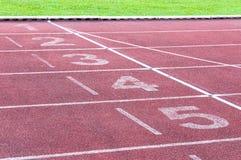 Numera o ponto de partida na pista de atletismo vermelha, na pista de atletismo e na grama verde Foto de Stock Royalty Free