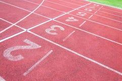 Numera o ponto de partida na pista de atletismo vermelha, na pista de atletismo e na grama verde Fotos de Stock Royalty Free