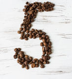 Numeral  from the grains of coffee on a light wooden background. Selective focus. Laid number five grains of coffee on light background of the old board Royalty Free Stock Photos