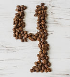 Numeral  from the grains of coffee on a light wooden background. Selective focus. Laid number four grains of coffee on light background of the old board Royalty Free Stock Photos