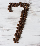 Numeral  from the grains of coffee on a light wooden background. Selective focus. The number seven Laid grains of coffee on light background old board Royalty Free Stock Images